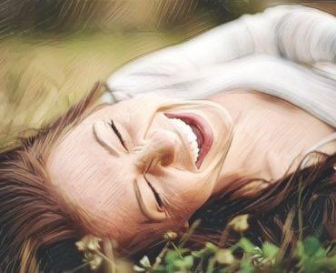 Una mujer tirada en el parque riendo a carcajadas y aprovechando los beneficios de la risa
