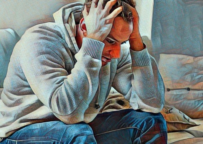 El desempleo causa depresión joven sentado que se toma la cabeza con sus manos