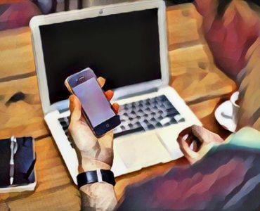 Hombre utilizando celular y laptop por addición al internet