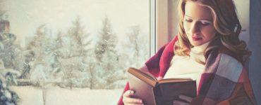 Mujer leyendo un libro cerca de la ventana