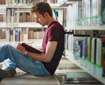 Persona joven introvertida en la biblioteca leyendo un libro