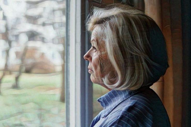 Persona mayor mirando por su ventana