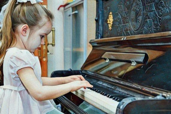 Niña tocando el piano desarrollando su inteligencia musical